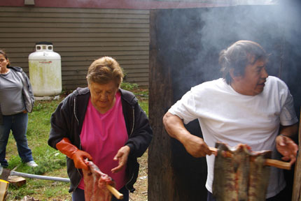 Cyrene Tooze and William Jones hanging their salmon in the smoke shed.