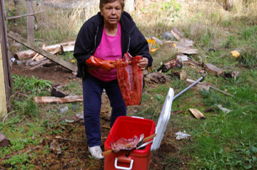 Cyrene Tooze prepares the salmon for hanging in the smoke shed.